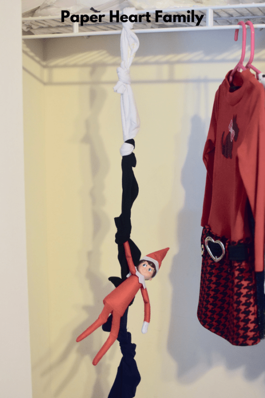 This elf on the shelf is ready for action and has made a rope out of socks to climb.