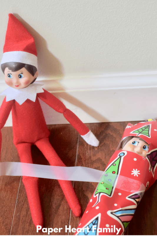 This mischievous Elf on the Shelf is wrapping her elf friend up. I wonder what he did?